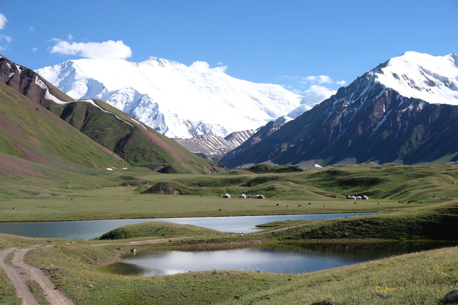 Berglandschaft mit Seen und einem Jurtencamp vor dem Peak Lenin.