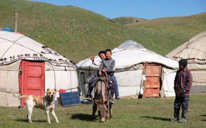 Zwei Jungen reiten vor kirgisischen Jurten auf einem Esel.