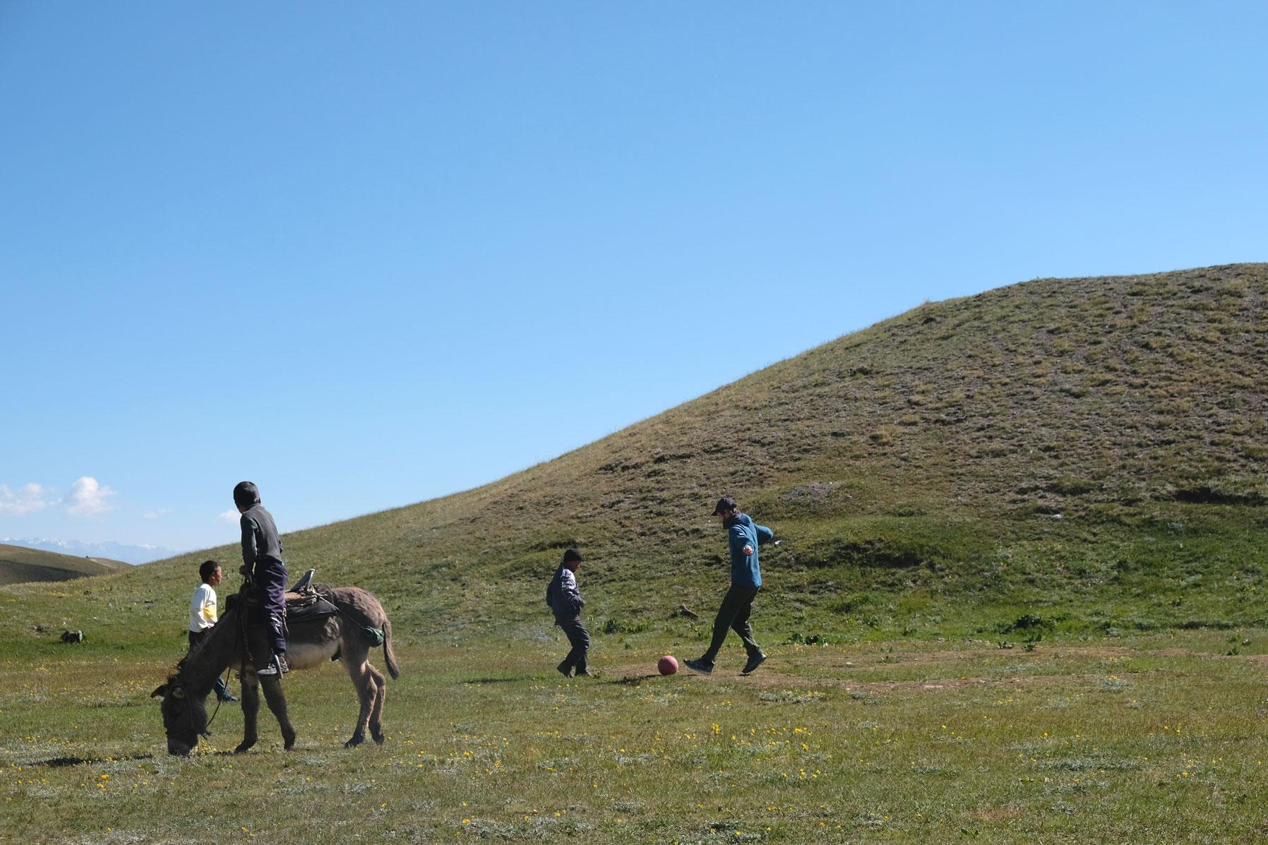Sebastian spielt mit zwei Jungs Fußball. Ein Junge sitzt auf einem Esel und schaut zu.