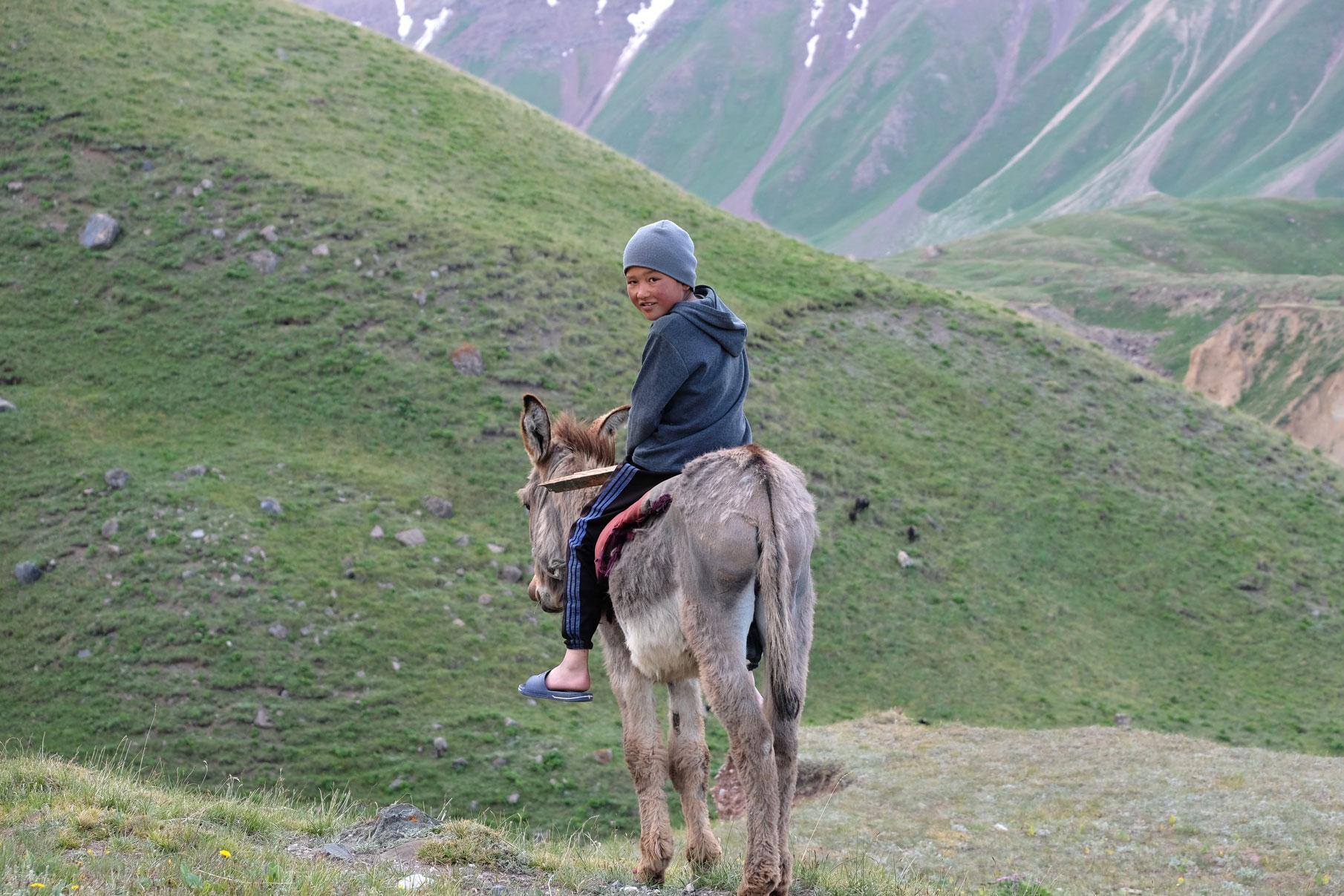 Ein Junge sitzt auf einem Esel.