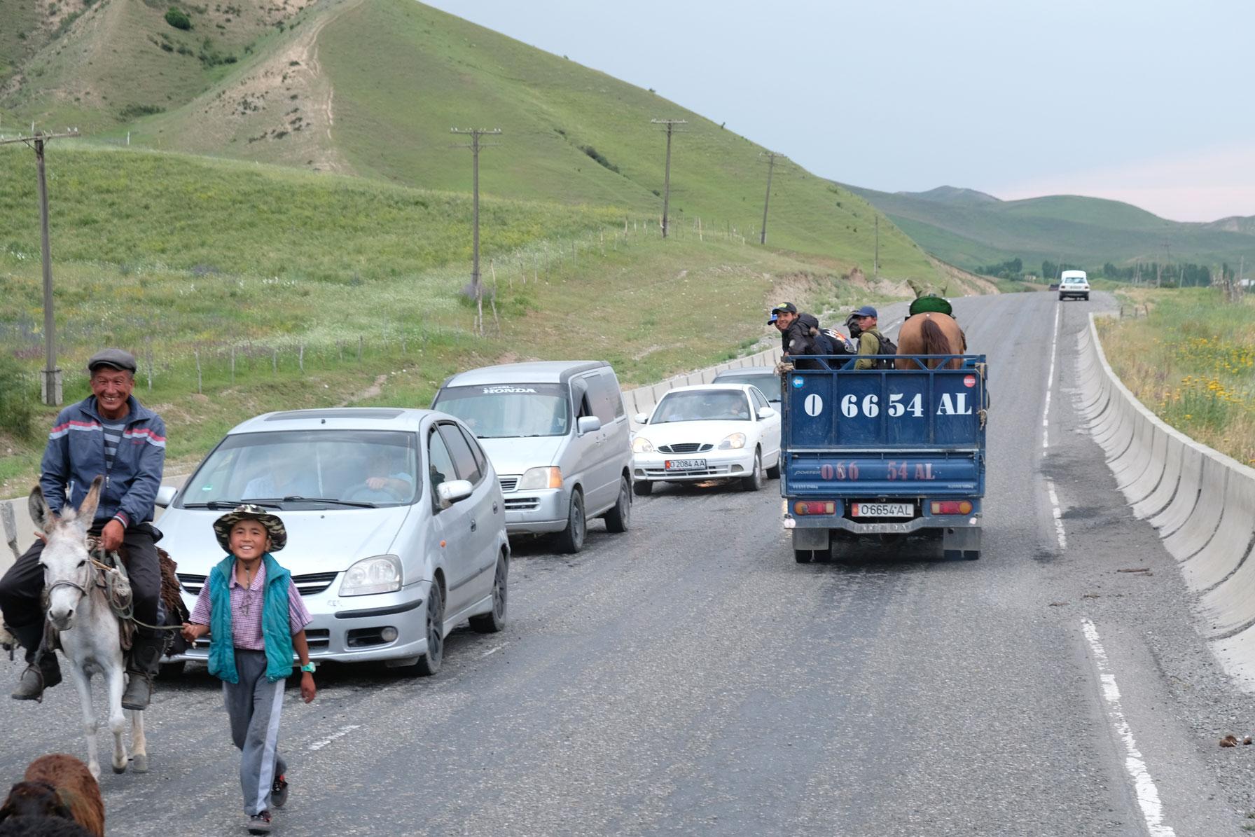 Autos auf einer Straße werden von einem Mann auf einem Esel aufgehalten.