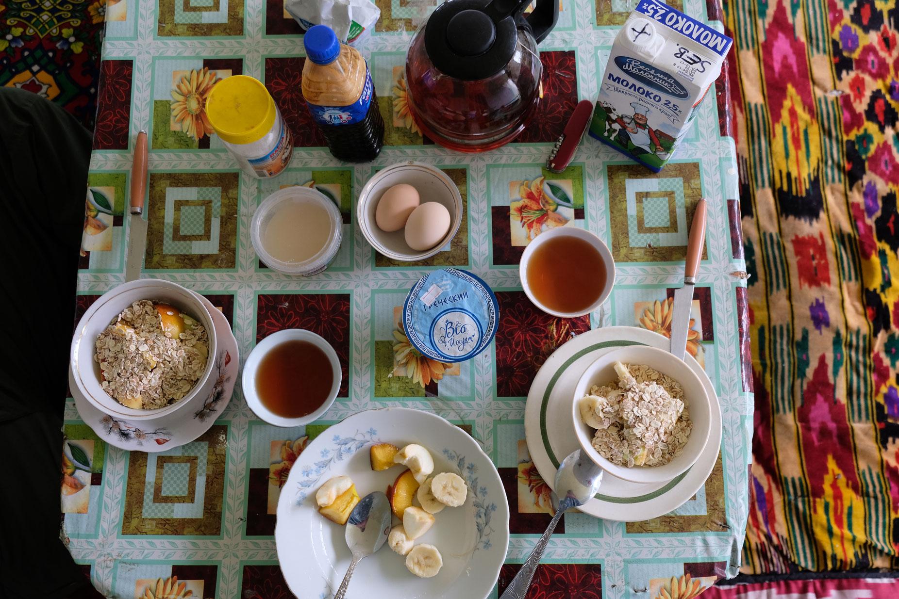 Frühstückstisch mit Eiern, Müsli, Obst und Tee.