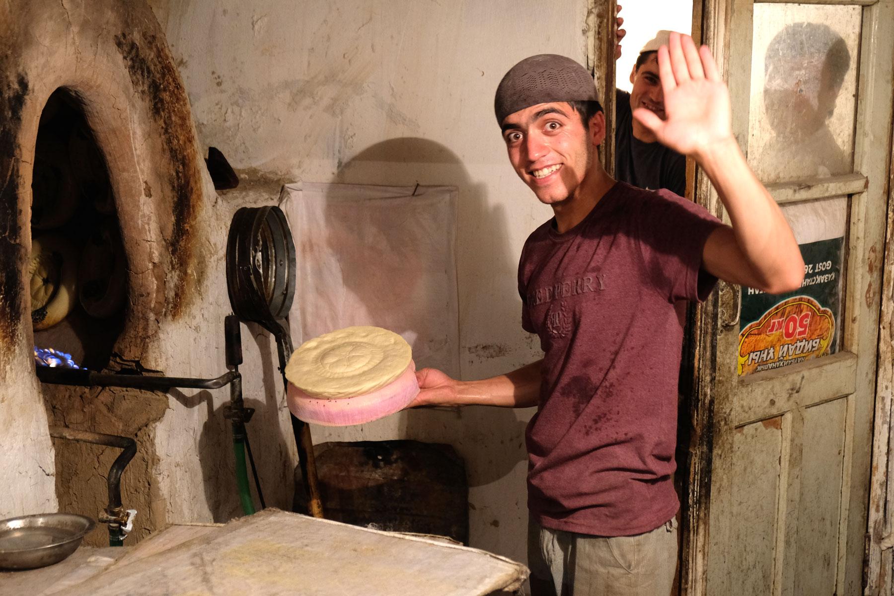 Ein junger Mann hält ein ungebackenes Brot in der Hand.