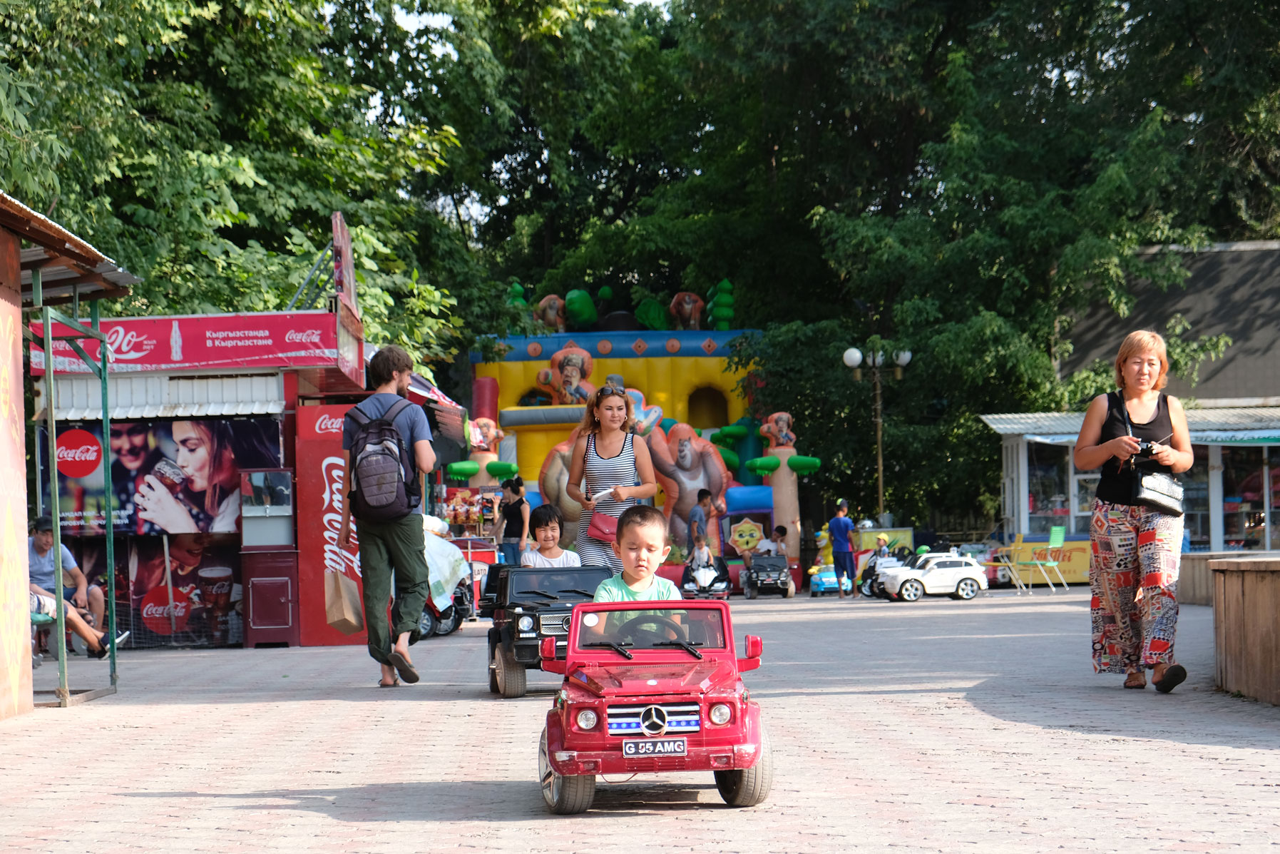 Zwei Kinder sitzen in ferngesteuerten Miniaturautos.