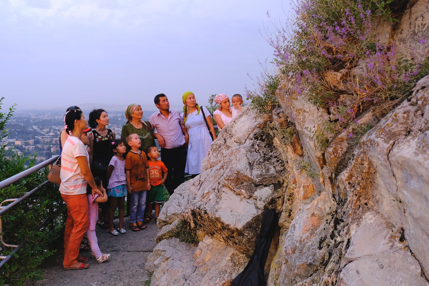 Eine kirgisische Familie schaut auf einen Felsen am Sulaiman-Too.