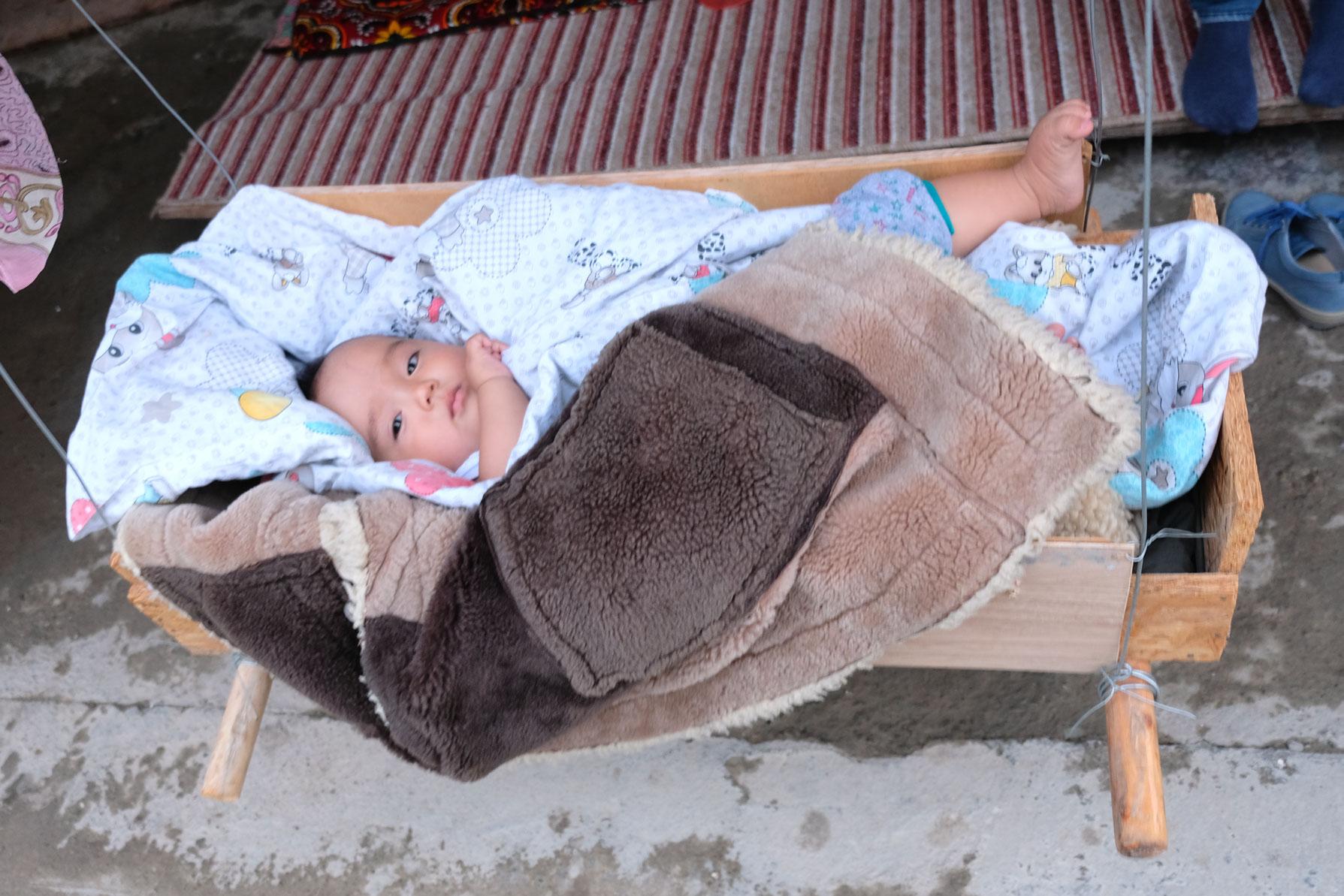 Ein Kleinkind in einer Wiege.