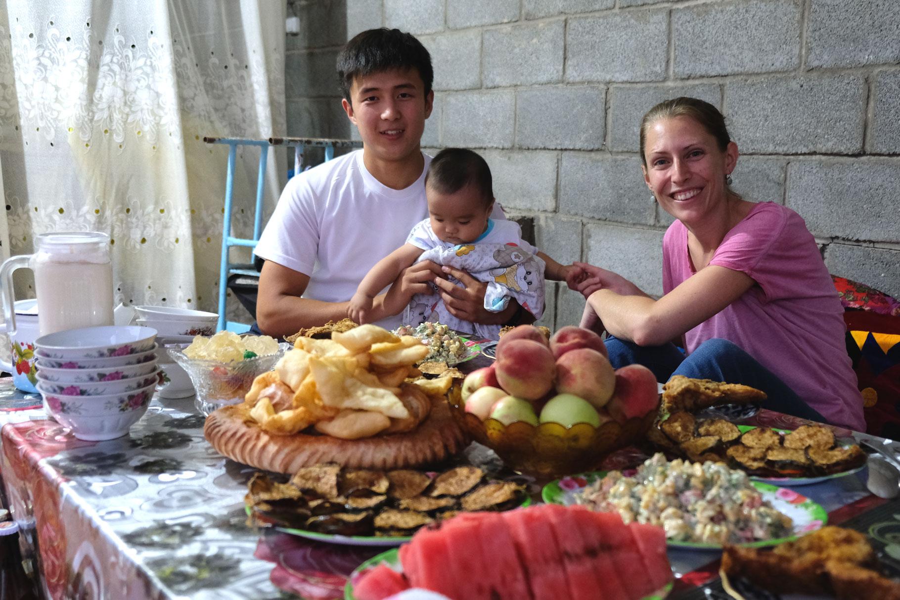 Leo mit Zhumabai und einem Kleinkind an einem Tisch mit Essen.