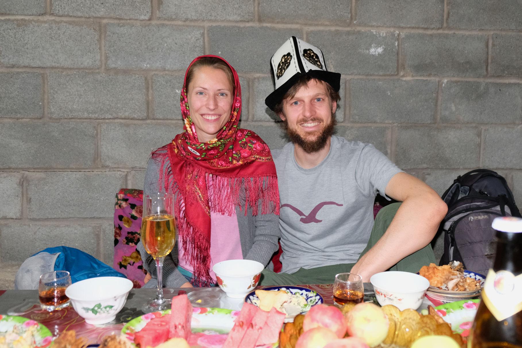 Leo mit Kopftuch und Sebastian mit traditionellem Kalpak sitzen an einem gedeckten Tisch.