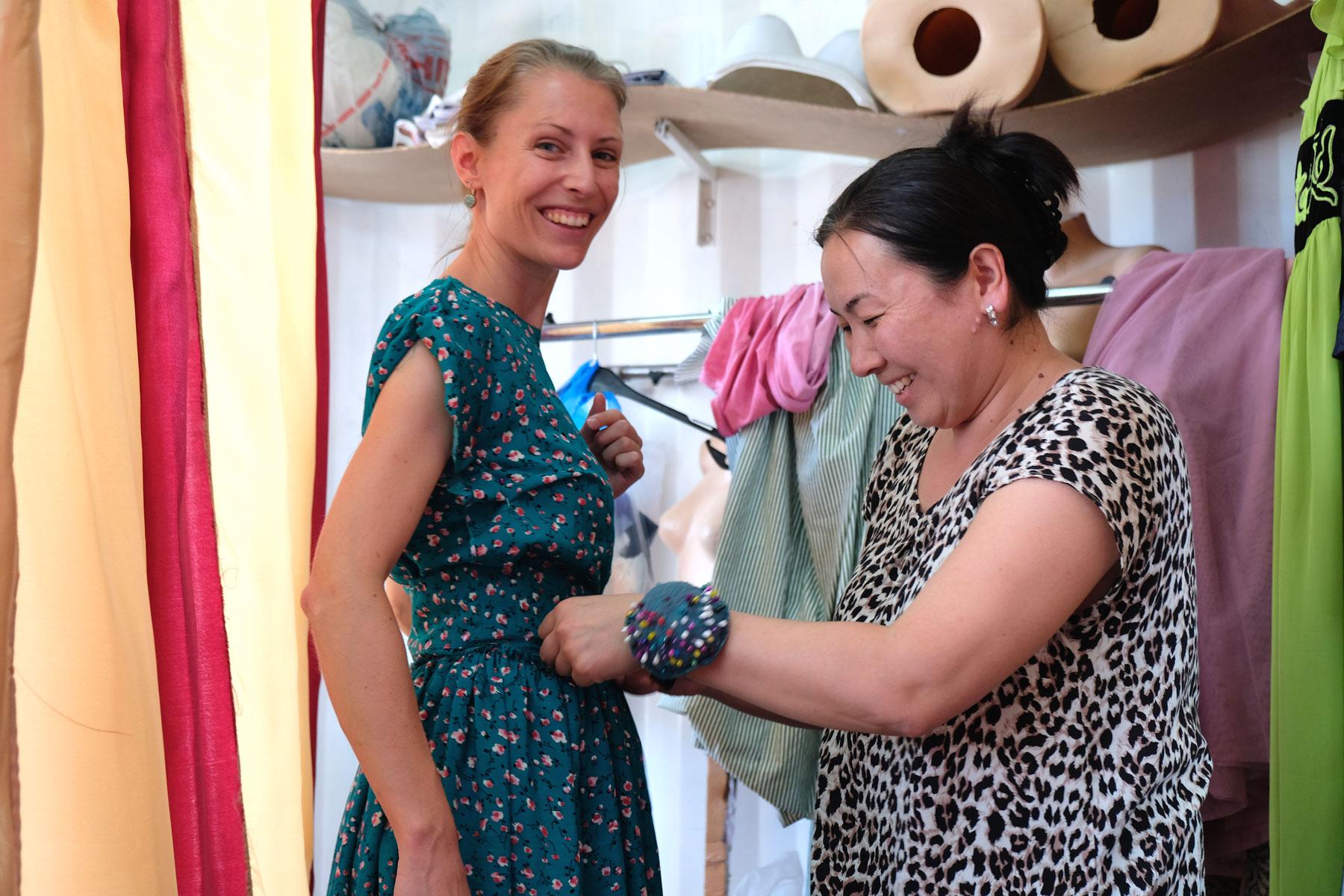 Leo probiert mit einer Schneiderin ein Kleid an.