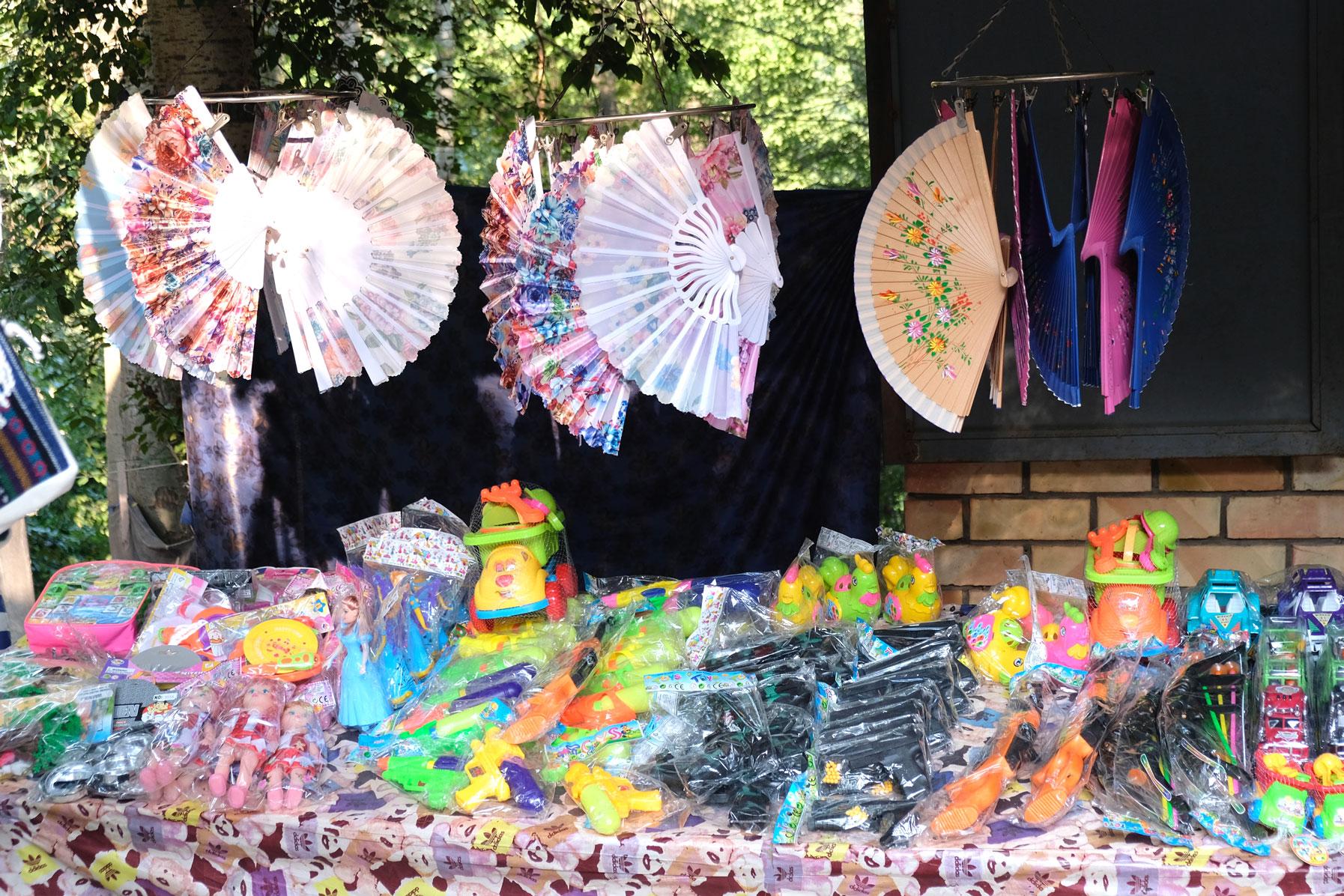 Fächer und Souvenire aus Plastik an einem Verkaufsstand.