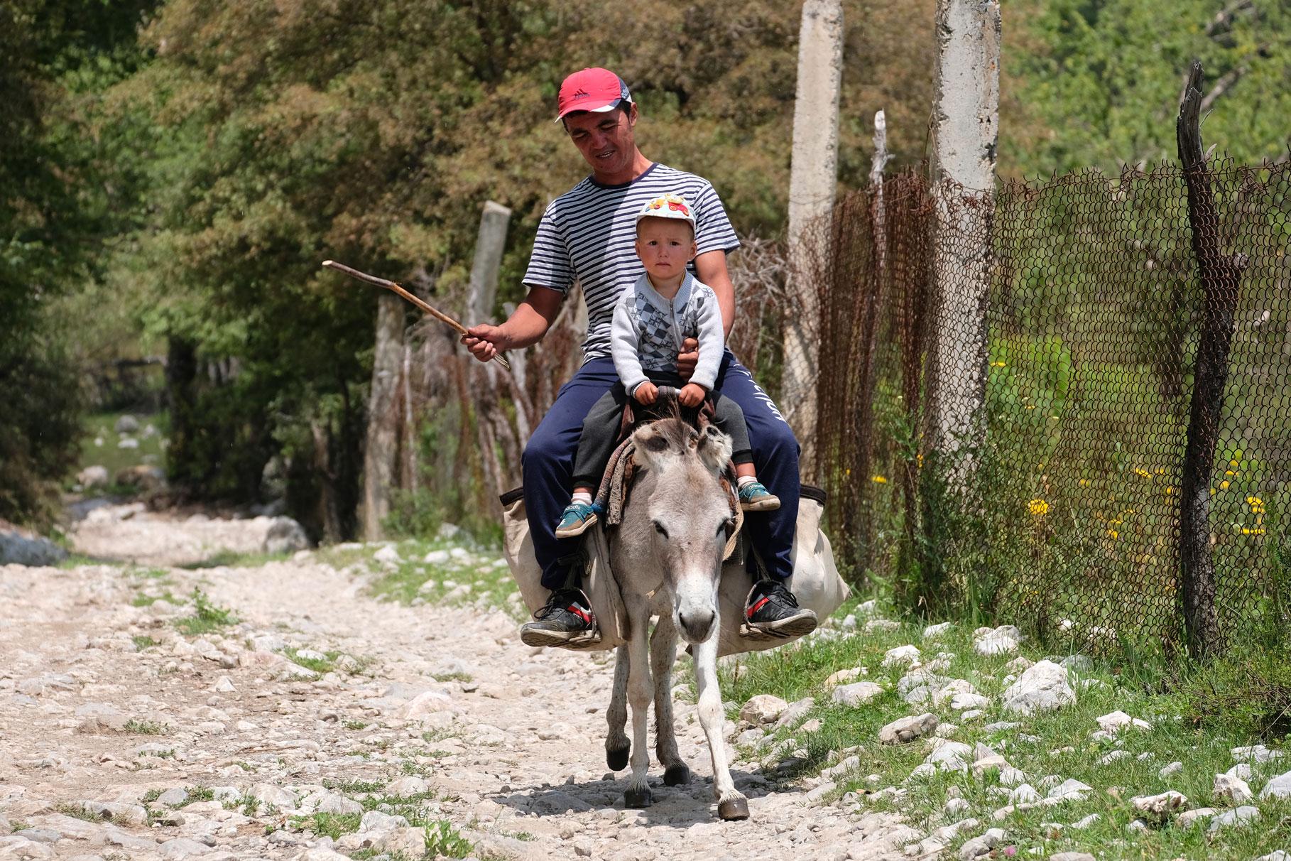 Ein Mann und ein Junge reiten auf einem Esel.
