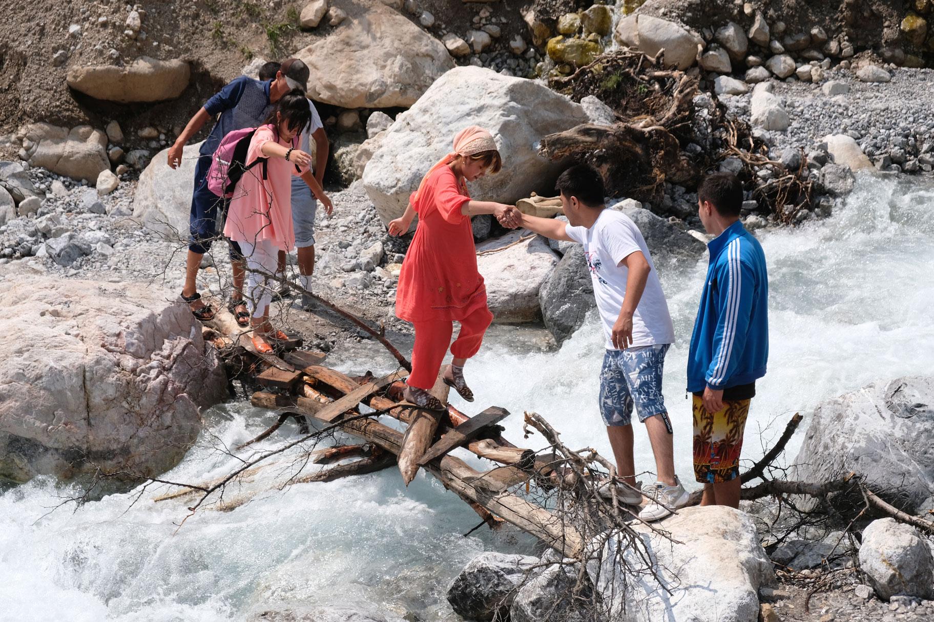 Eine Gruppe Jugendlicher geht über einen Holzsteg über einen Gebirgsbach.