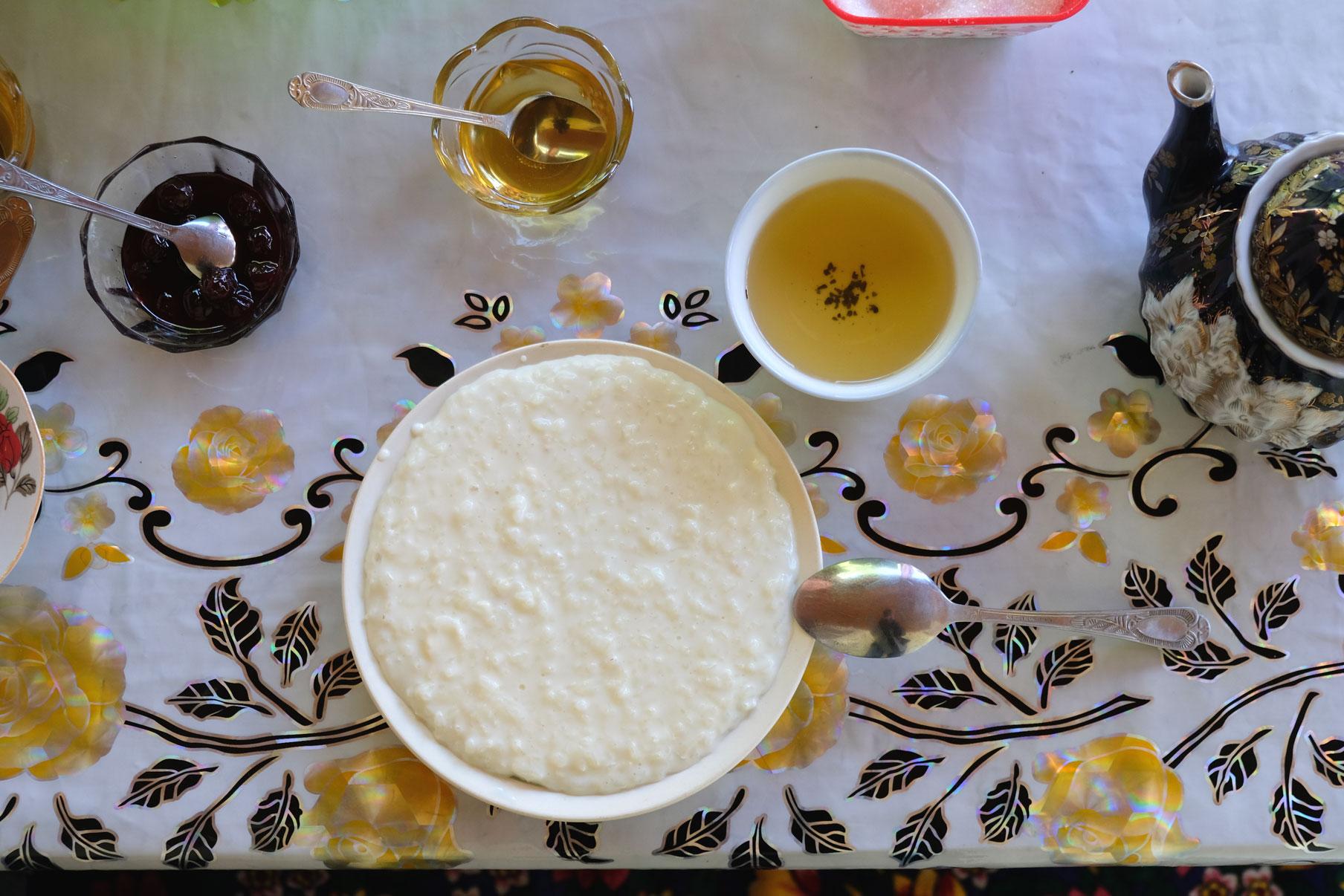 Milchreis, Tee und Honig auf einem Tisch.