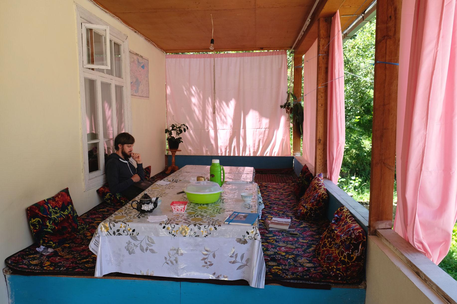 Sebastian sitzt am Tisch eines Homestays in Arslanbob.
