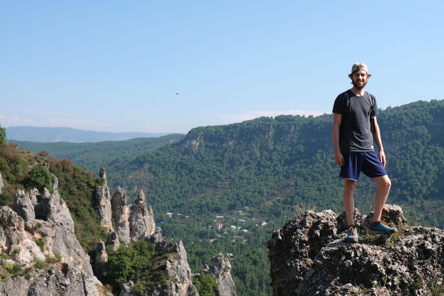 Sebastian steht auf einem Felsen in den Bergen.