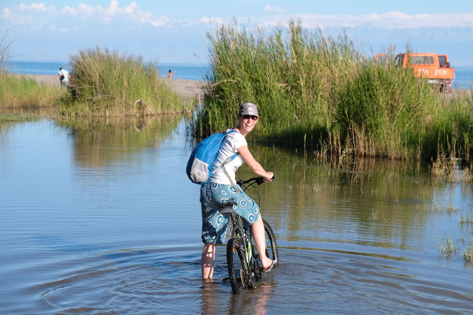 Leo steht mit einem Fahrrad im Wasser.
