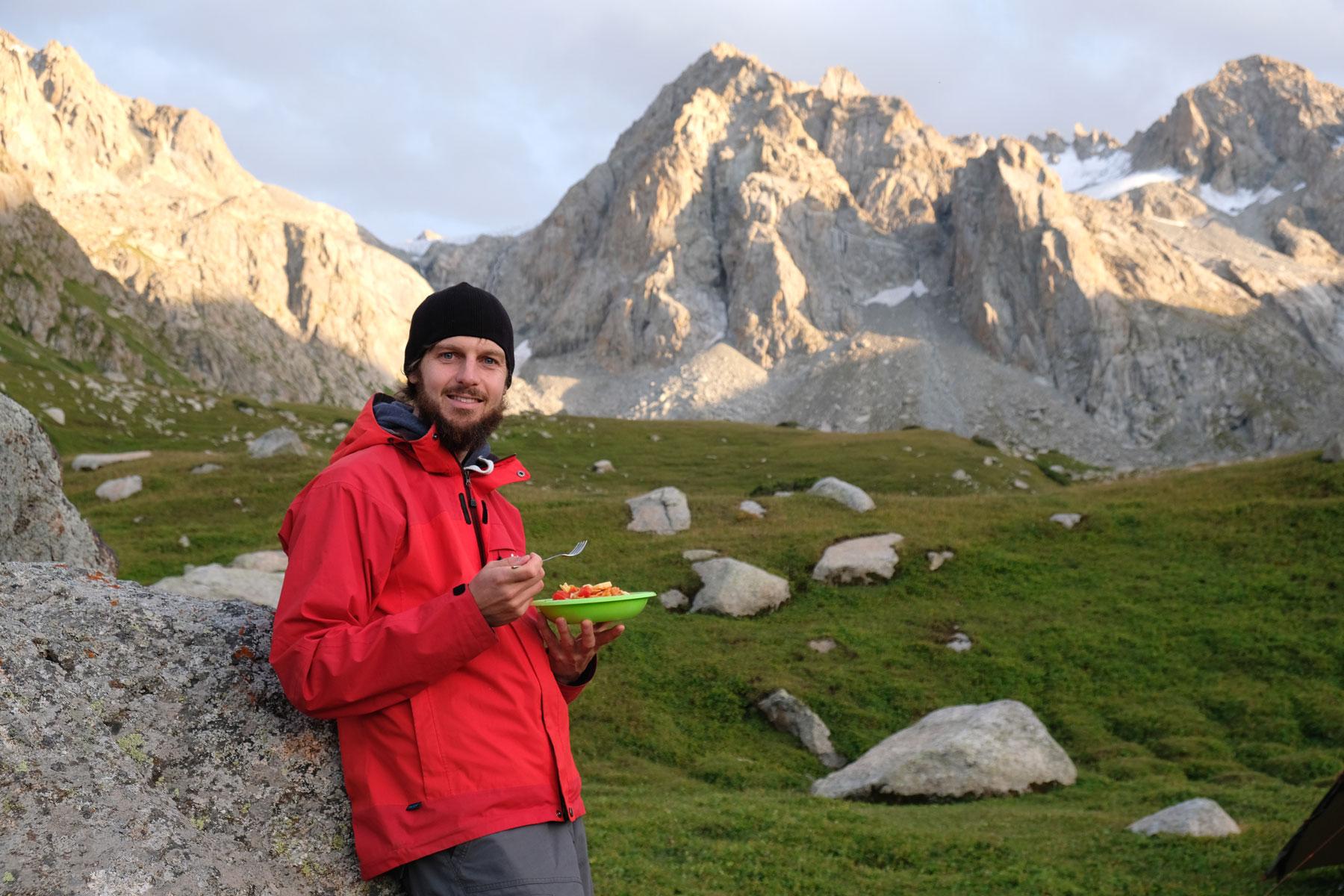 Sebastian lehnt sich im Gebirge an einen Felsen und hält einen Teller in der Hand.