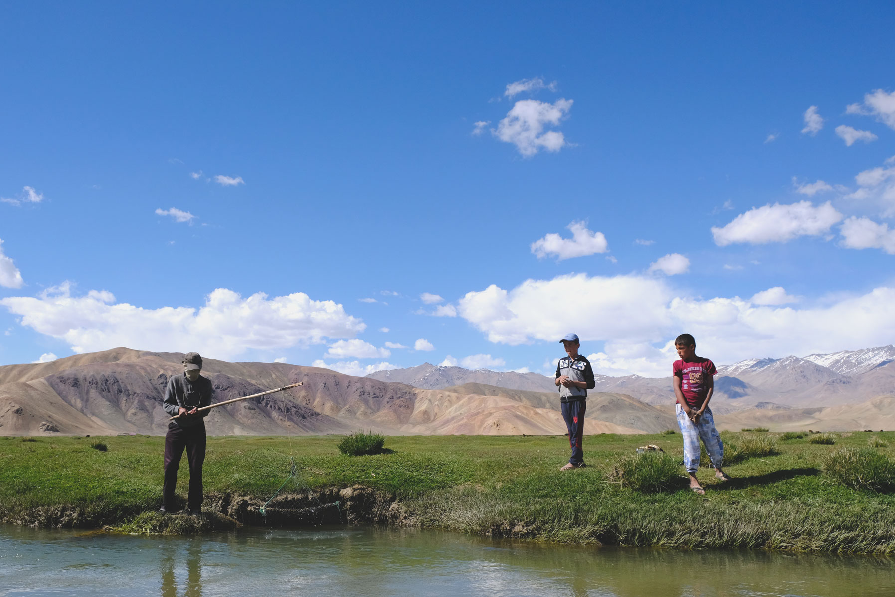 Ein Mann angelt an einem Fluss. Zwei Jungen schauen zu.
