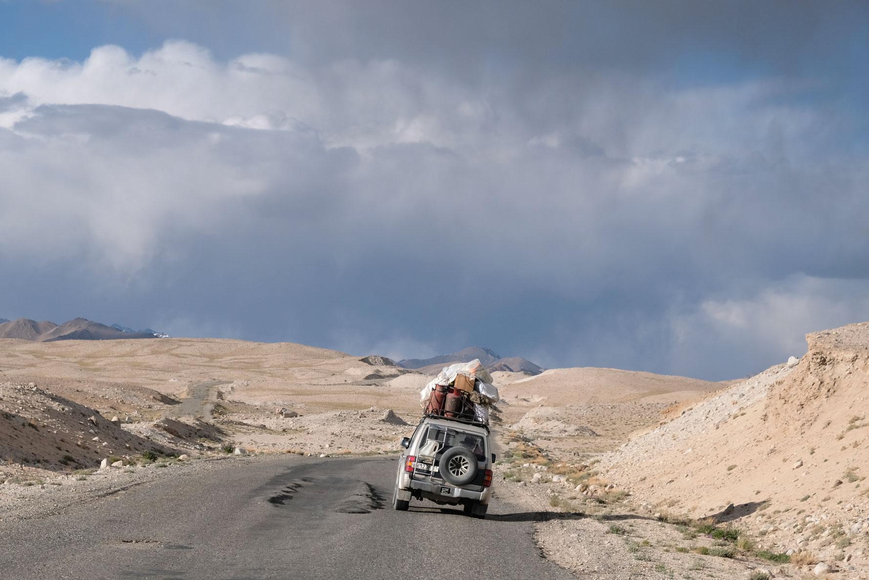 Ein hoch belandener Geländewagen und Spurrillen auf dem Pamir Highway.