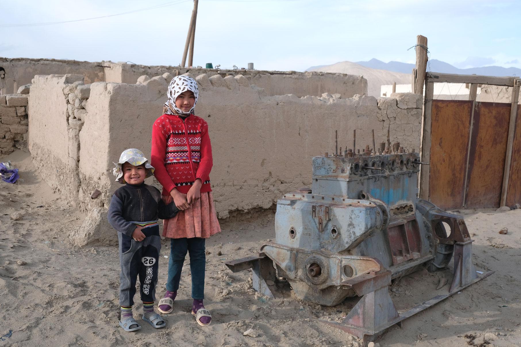 Zwei Kinder neben einem alten Motor in Rangkul.