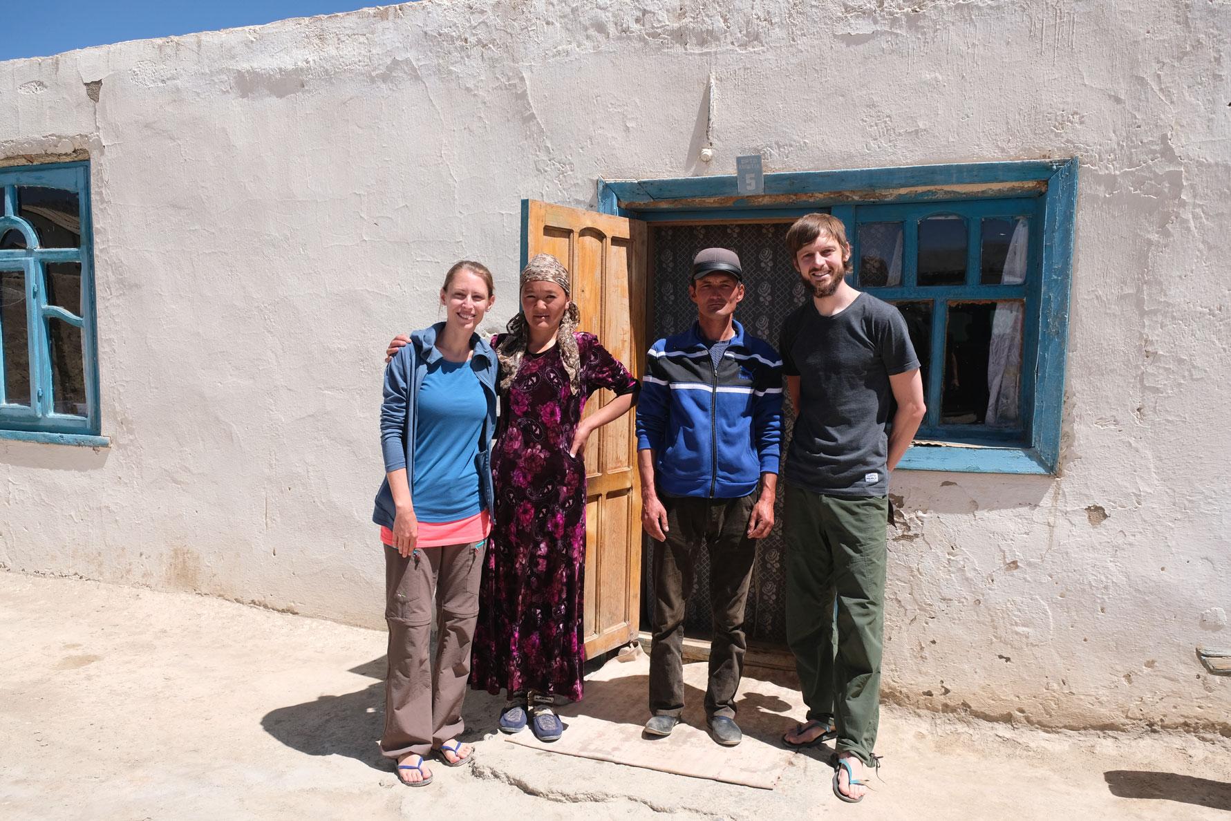 Leo und Sebastian mit zwei Personen vor einem Homestay in Rangkul im Pamirgebirge.