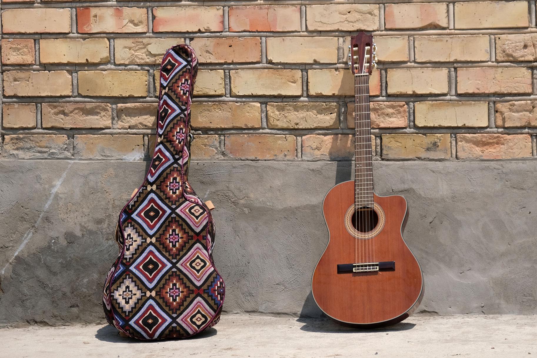 Eine Gitarrenhülle und eine Gitarre lehnen an einer Wand.