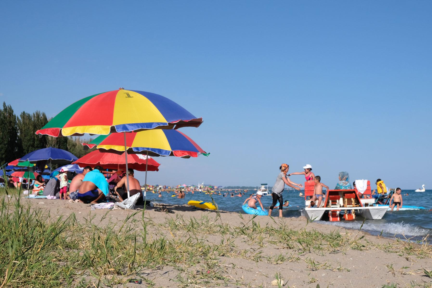 Sonnenschirme am Strand des Issyk-Kul Sees bei Tamchy.