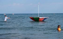 Ein Mann watet im Issyk-Kul See und versucht, einen davonschwimmenden Sonnenschirm einzufangen.