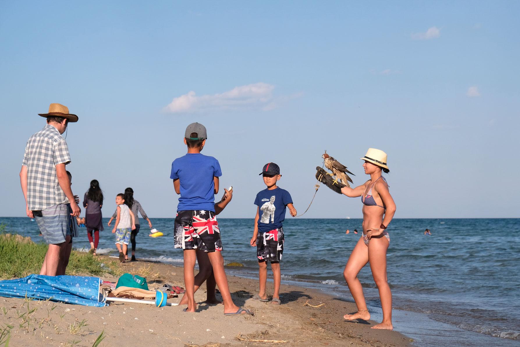 Eine Frau in Bikini hält am Uder des Issyk-Kul einen Falken auf dem Arm.