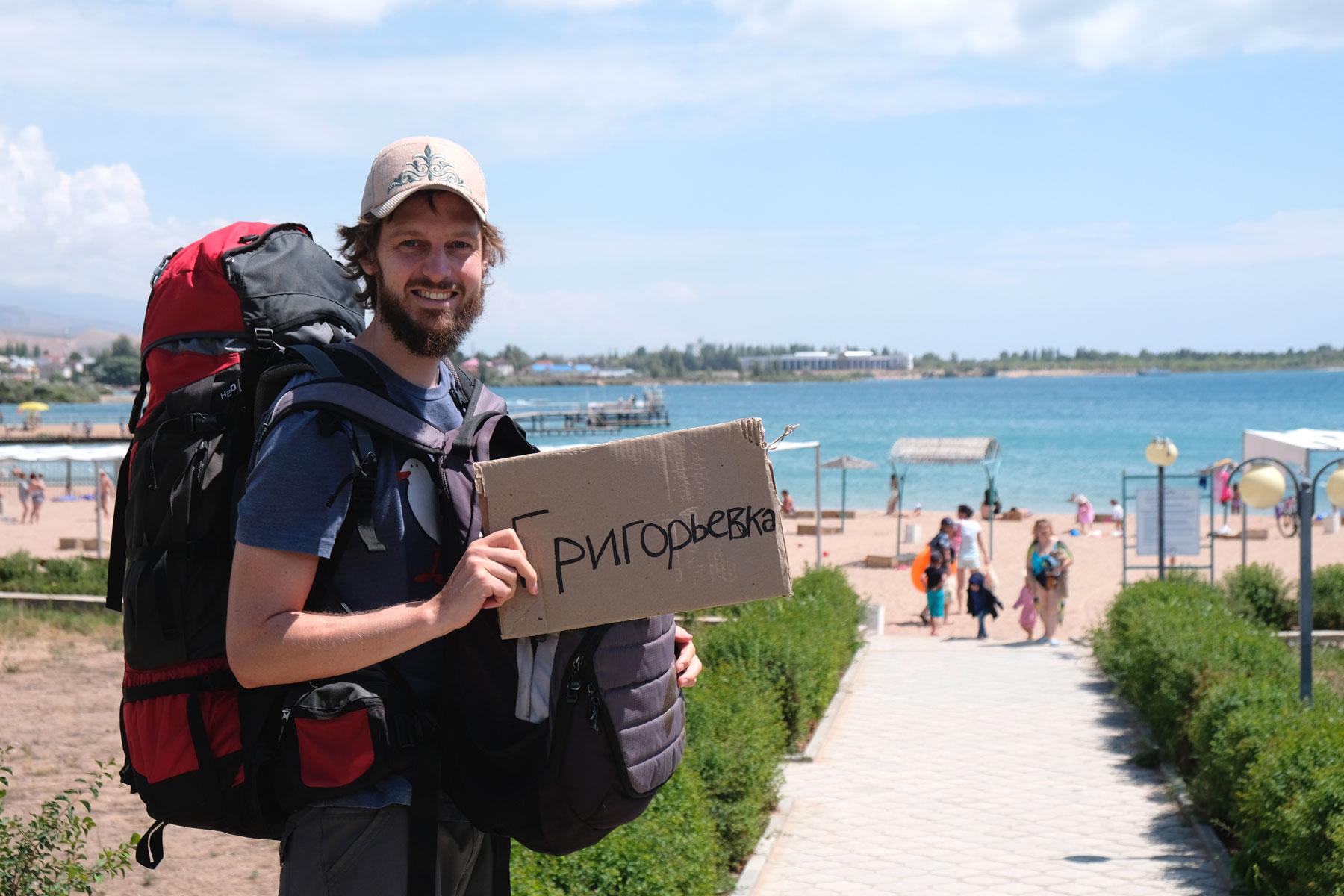 """Sebastian hat einen großen Reiserucksack auf dem Rücken und hält ein Schild, auf dem """"Grigorievka"""" mir kyrillischen Buchstaben geschrieben steht."""