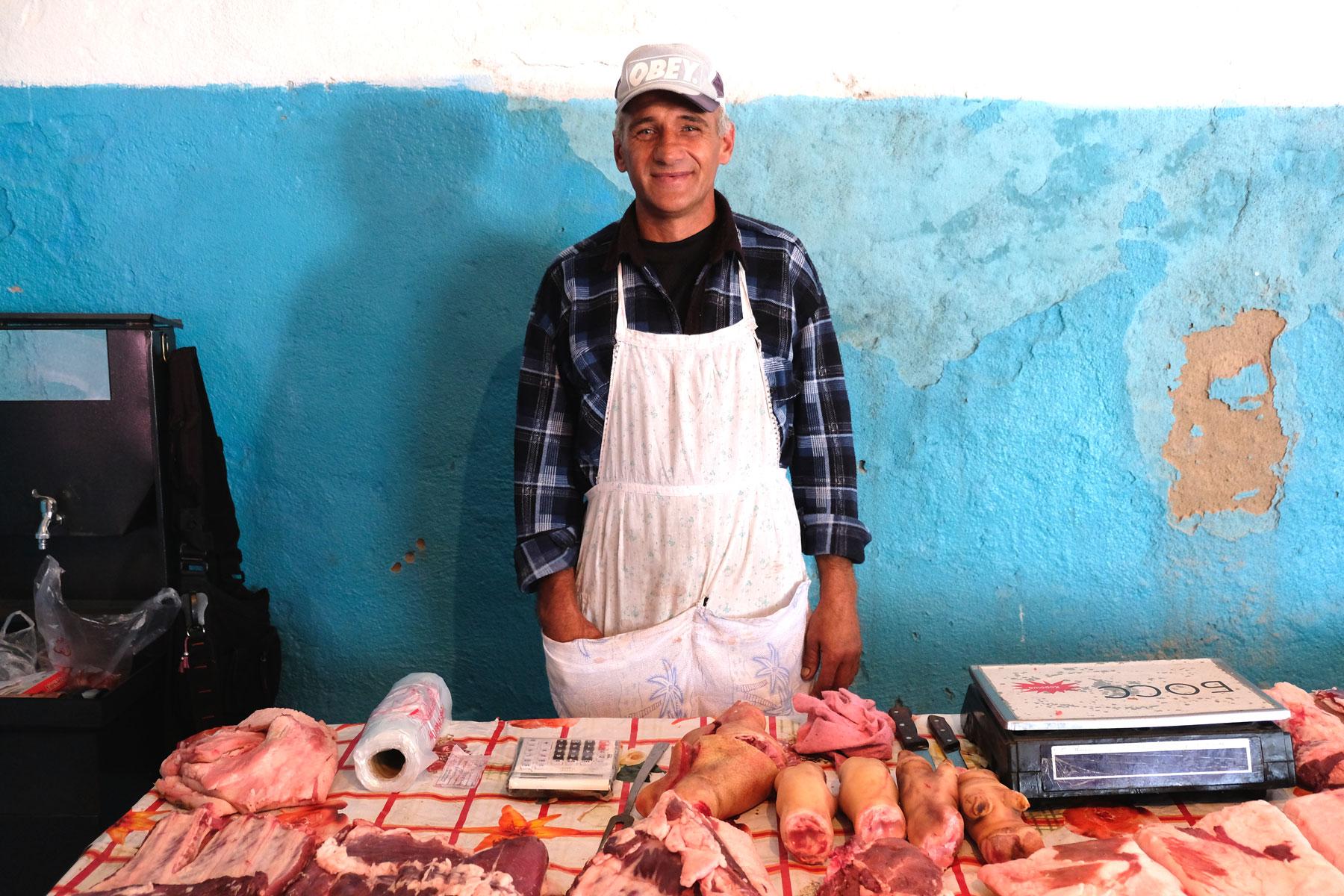 An einem Marktstand wird Fleisch verkauft.