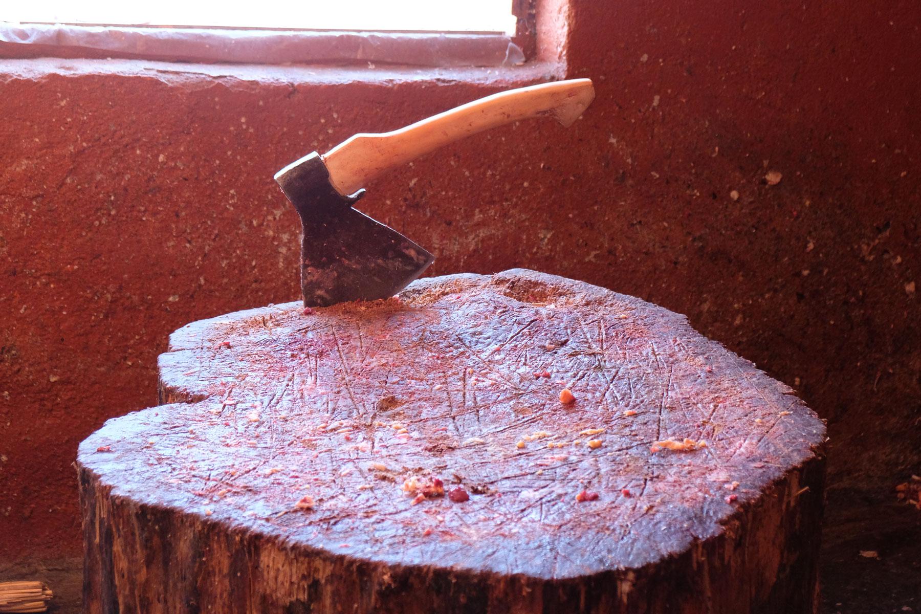 Eine Axt steckt in einem Baumstamm.