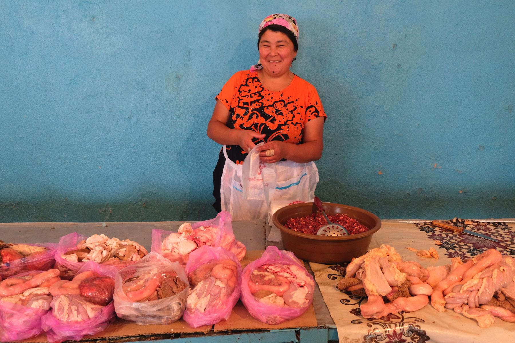 Eine Kirgisin an ihrem Marktstand mit Fleischwaren.