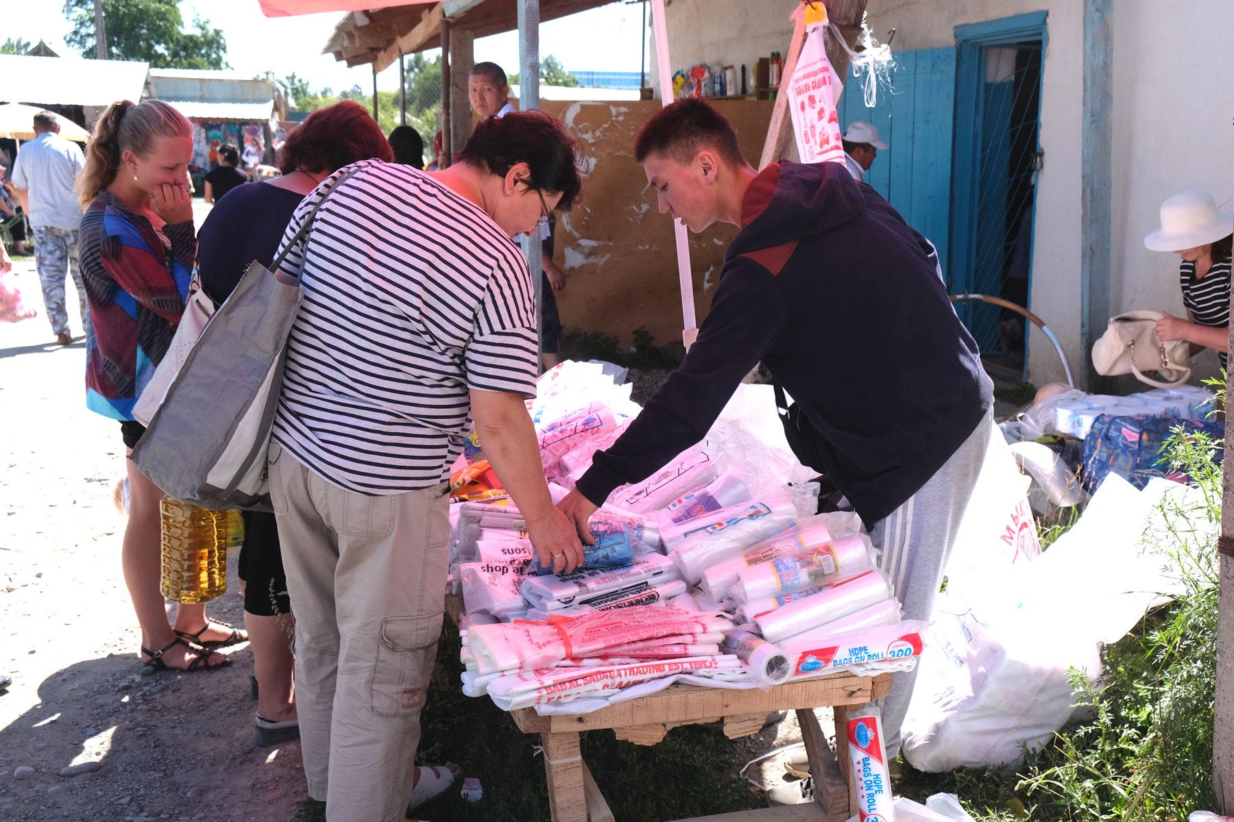 An einem Marktstand werden Plastiktüten verkauft.