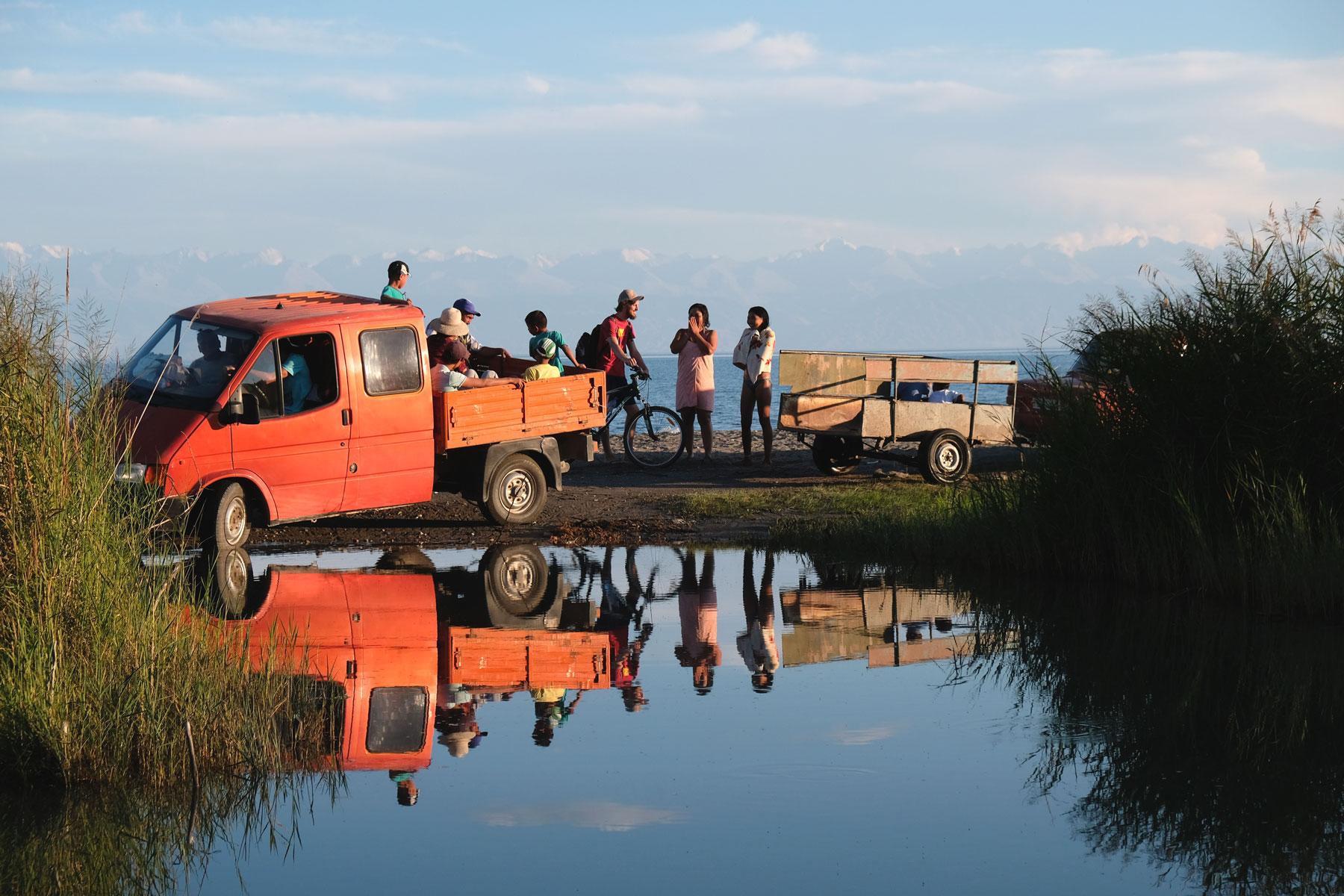 Ein roter Lieferwagen und Menschen am Rand einer riesigen Pfütze.