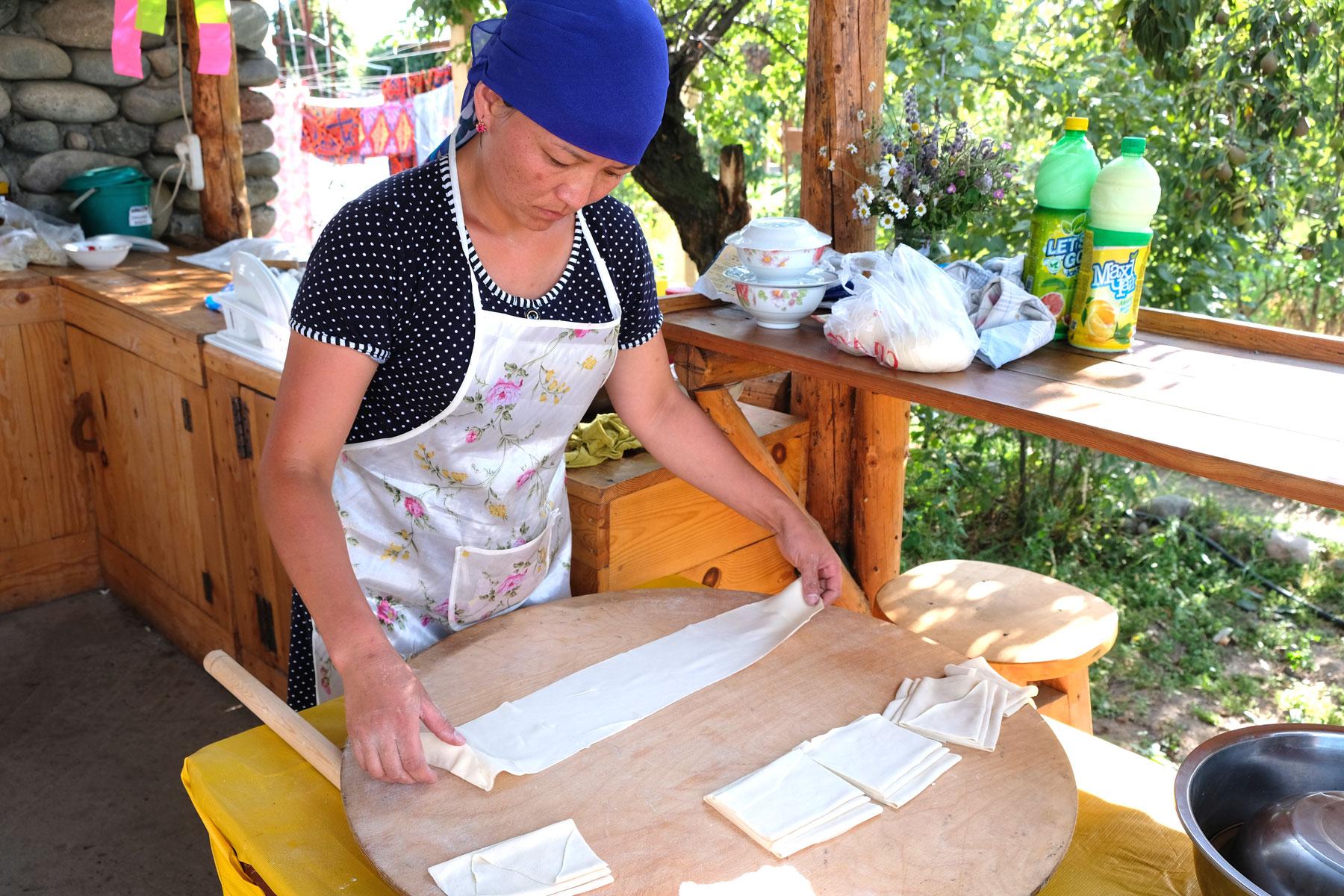 Eine kirgisische Frau bereitet Teig für Mantı zu.