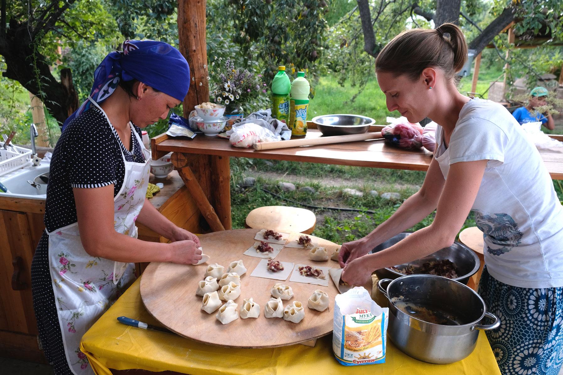 Eine kirgisische Frau und Leo falten Mantı.
