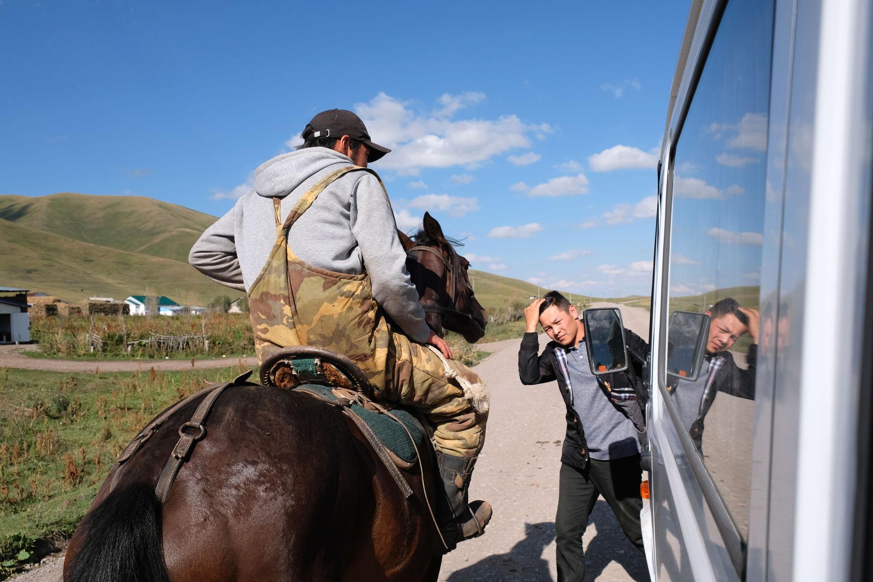 Reiter kommen ans Auto und geben Säcke hinen oder nehmen andere entgegen