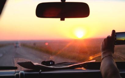 Jemand macht aus einem Auto heraus ein Handyfoto vom Sonnenuntergang.