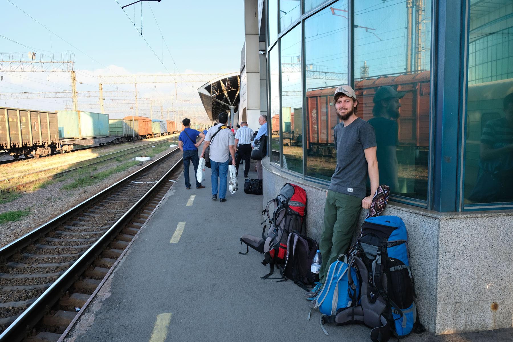 Sebastian steht neben Rucksäcken an einem Bahnsteig des Hauptbahnhofs von Almaty.