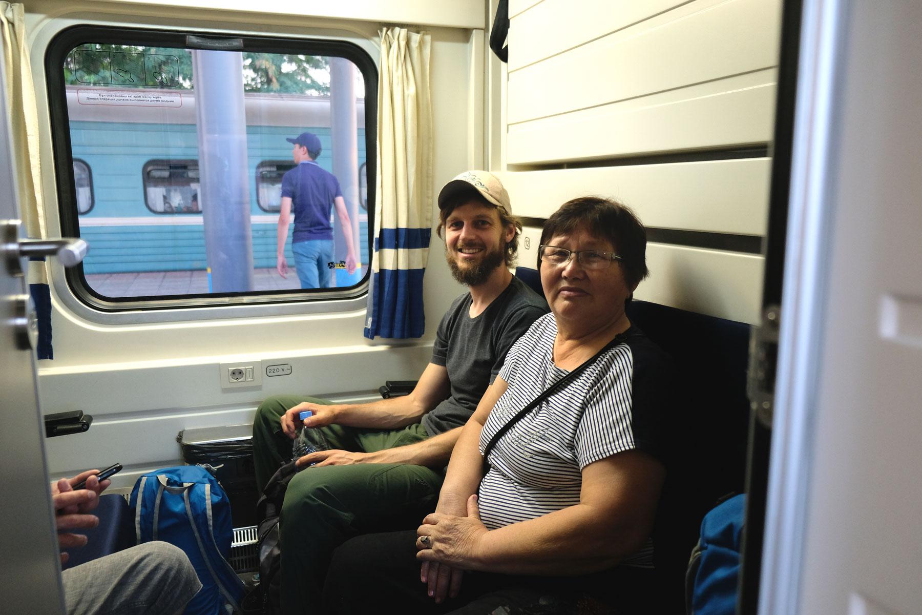 Sebastian sitzt neben einer kasachischen Frau in einem Zugabteil.