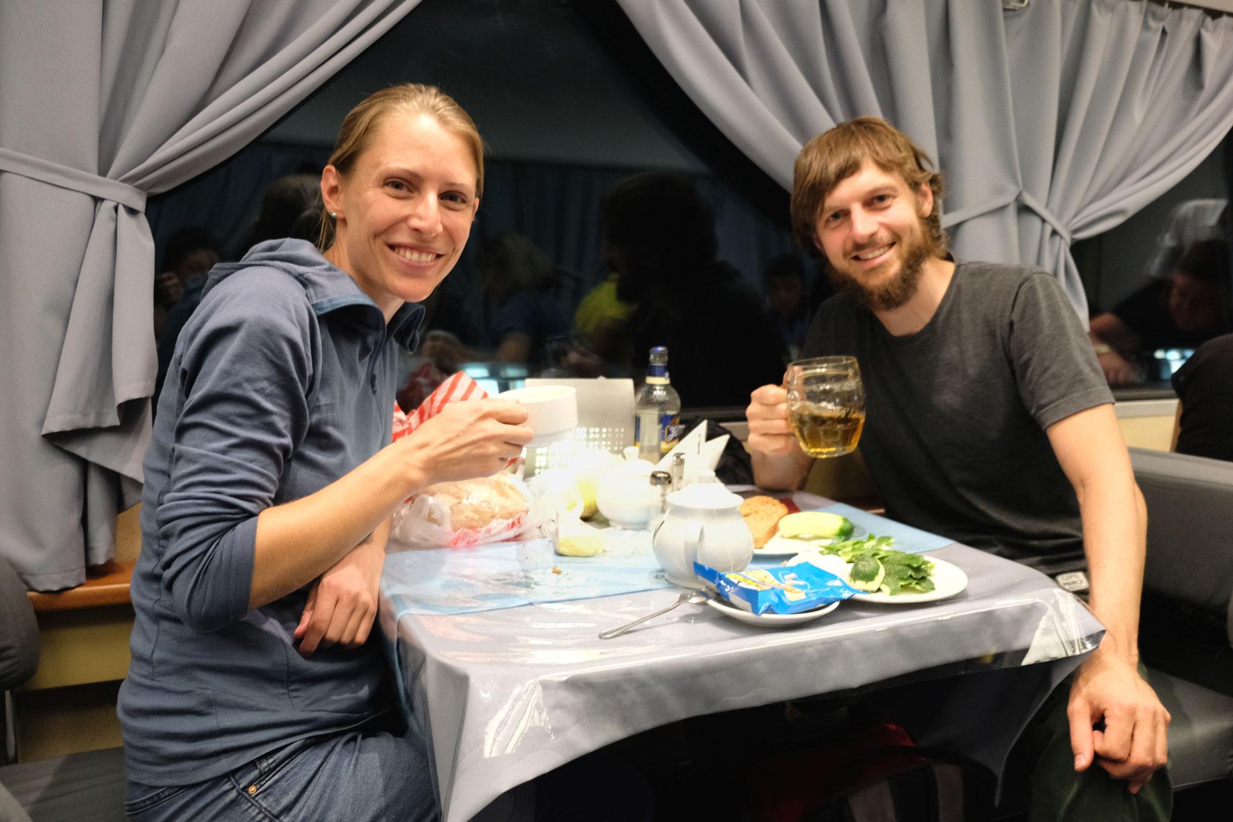 Leo und Sebastian essen im Speisewagen eines Zugs zu Abend.