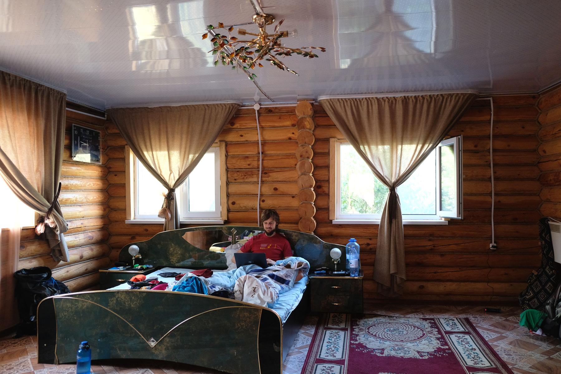 Sebastian sitzt im Bett in einer Holzhütte in Korgalzhyn.