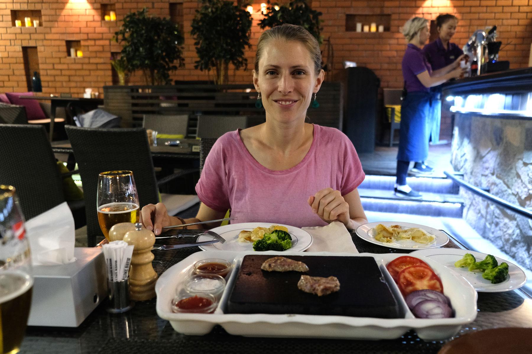 Leo in einem Restaurant. Auf dem Tisch steht eine Steinplatte, auf der Fleisch gebraten wird.