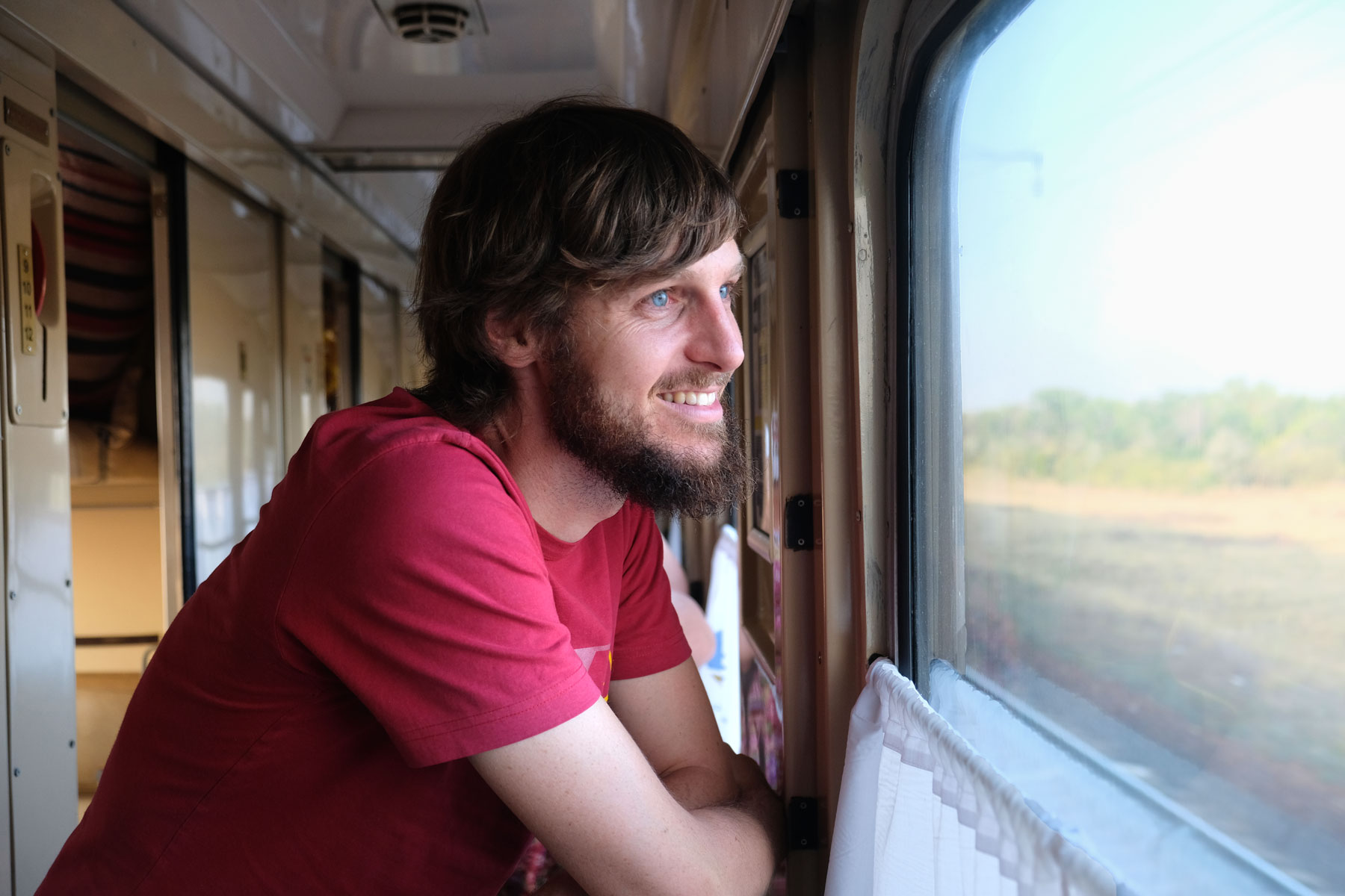 Sebastian schaut aus dem Fenster eines Zugs.