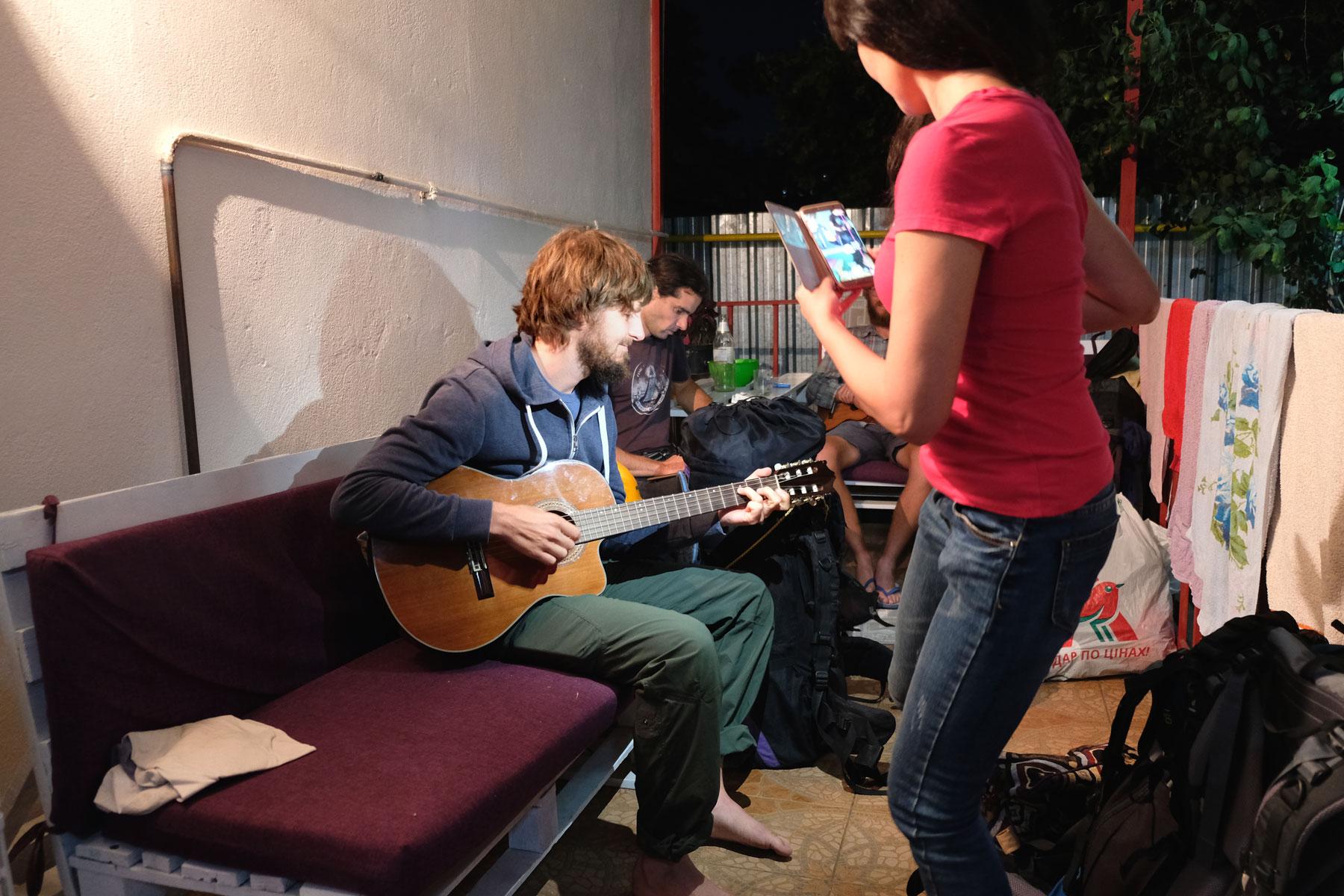 Sebastian spielt Gitarre. Eine Frau filmt ihn mit ihrem Smartphone.