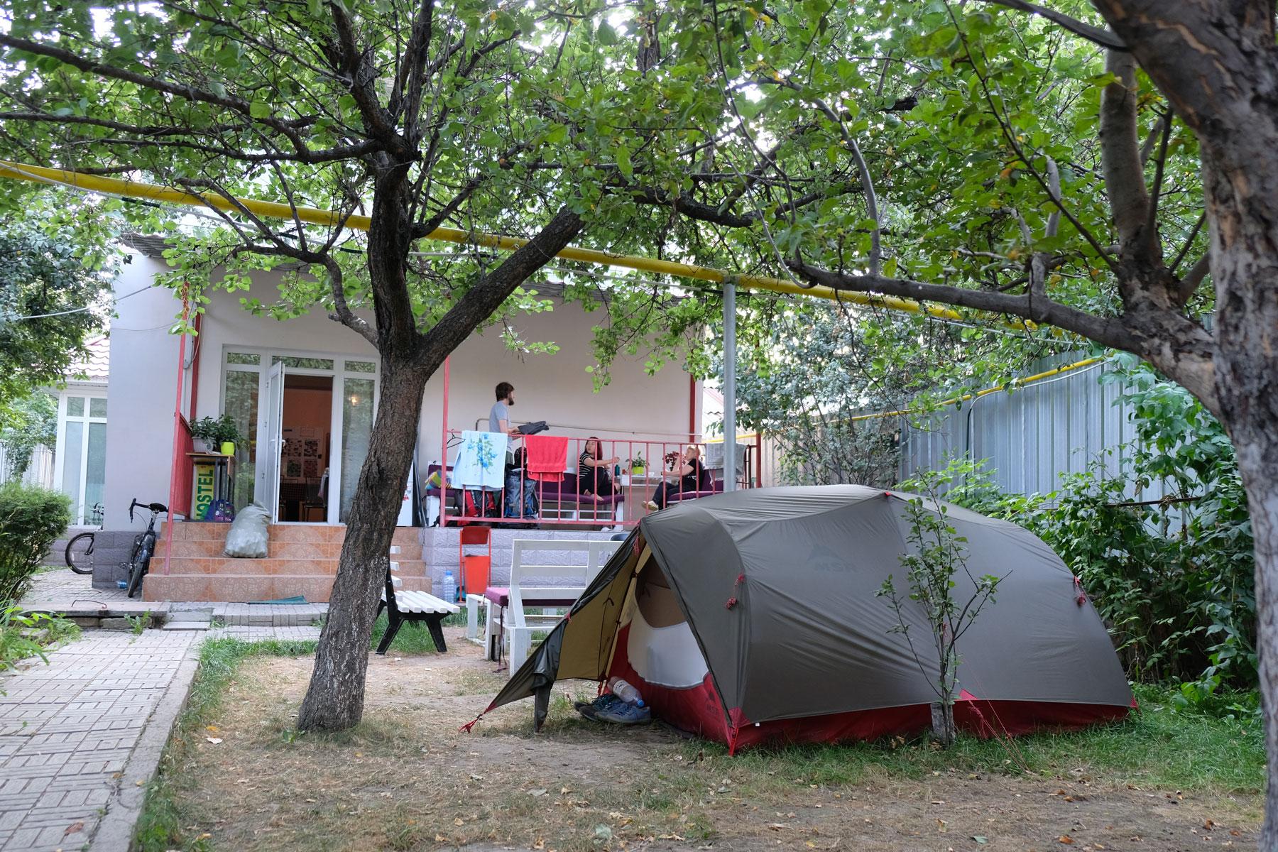 Ein Zelt steht im Garten eines Hostels.