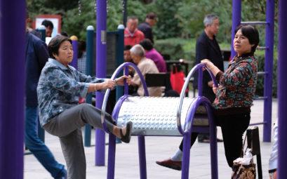 Chinesische Frauen machen Leibesübungen an einem Sportgerät im Park.