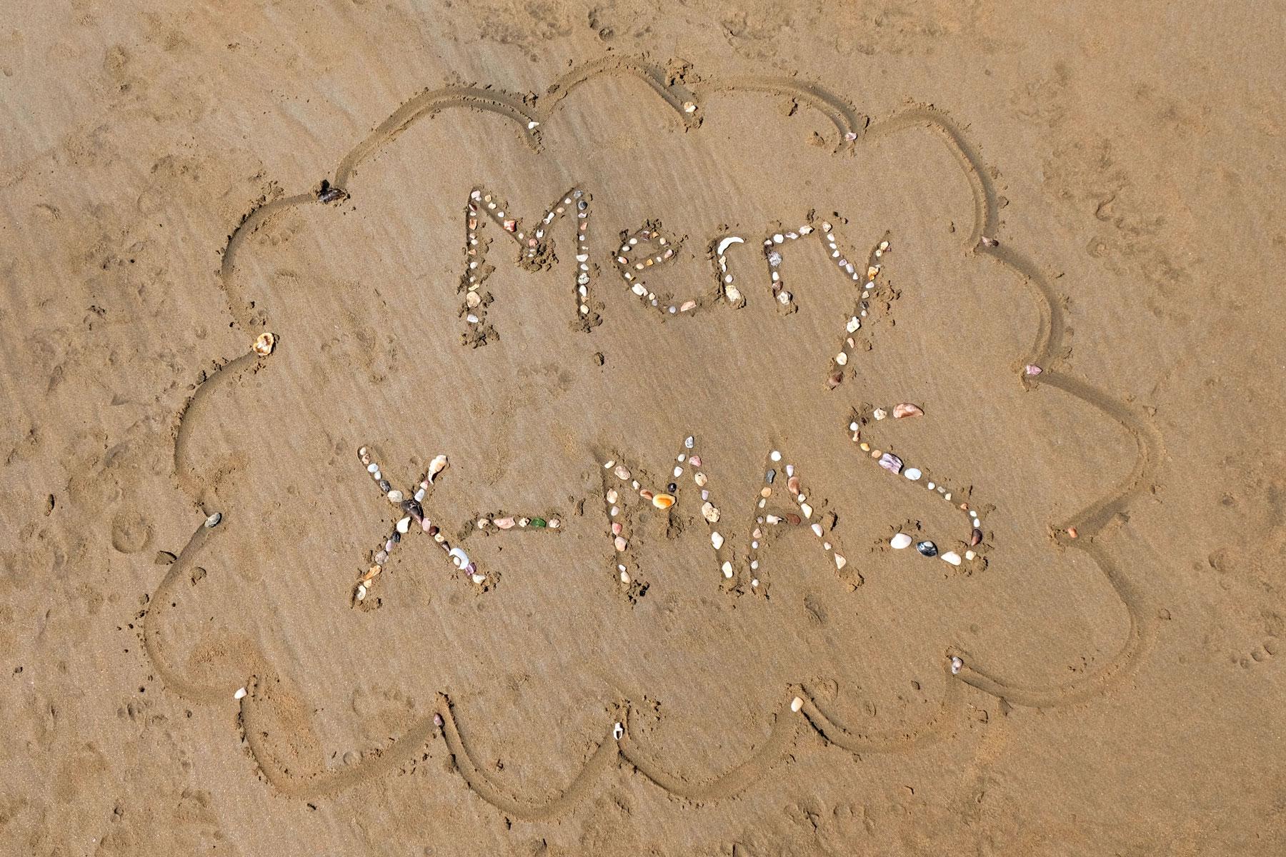 """Die Worte """"Merry X-Mas"""" mit Muscheln auf Sand gelegt."""