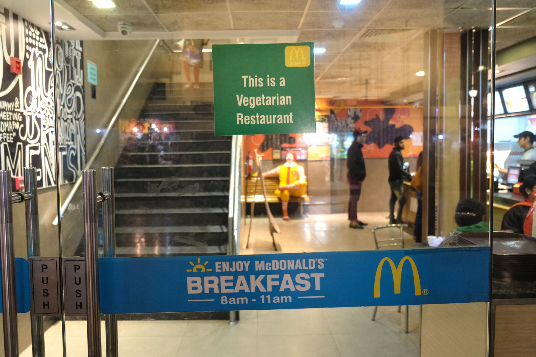 Eingangstür zu einer McDonald's Filiale in Amritsar. Ein Schild weist darauf hin, dass dies ein vegetarischer McDonald's ist.